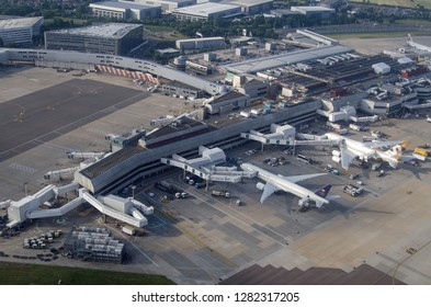 LONDON, UK - JUNE 12, 2018: Aerial view of planes from Saudia and Emirates Airline parked at Terminal 4 of London's Heathrow Airport on a sunny summer morning.  The Crown Plaza hotel is just beyond.