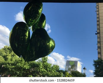 London / UK - June 14th 2018: Green heart helium balloons fly on the anniversary of the Grenfell Tower fire with the burnt tower in the background.