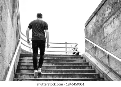 London, UK - June 15 2018: Young man wearing casual clothes climbing the stairs. Success and business concept.