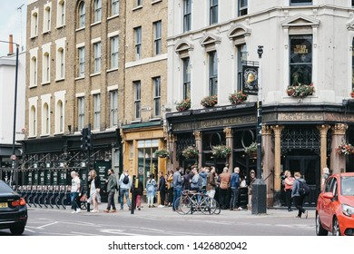 London, UK - June 15, 2019: People standing and drinking outside The Ten Bells pub in Shoreditch, East London. The pub is famous for its supposed association with two victims of Jack the Ripper.