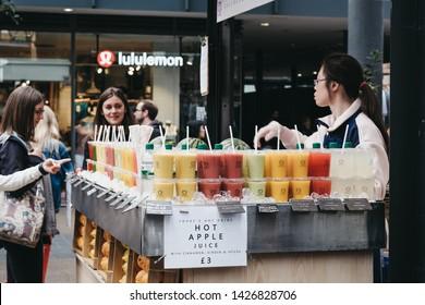 London, UK - June 15, 2019: People buying fresh juice at Spitalfields Market, one of the finest surviving Victorian Market Halls in London with stalls offering fashion, antiques and food.