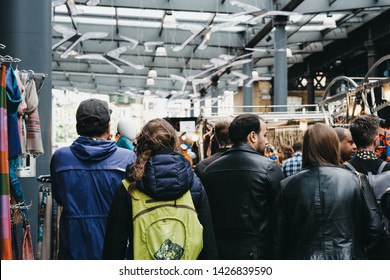 London, UK - June 15, 2019: People walking between the stalls inside Spitalfields Market, one of the finest surviving Victorian Market Halls in London with stalls offering fashion, antiques and food.