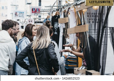 London, UK - June 15, 2019: People browsing items at stalls inside Spitalfields Market, one of the finest surviving Victorian Market Halls in London with stalls offering fashion, antiques and food.