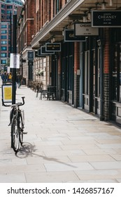 London, UK - June 15, 2019: Parked bicycle next to row of shops in Spitalfields Market, one of the finest surviving Victorian Market Halls in London with stalls offering fashion, antiques and food.