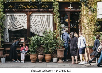 London, UK - June 15, 2019: People by the front entrance of Gloria, Italian restaurant in Shoreditch, London, famous for ivy-covered exterior walls and numerous plants in terracotta pots outside.