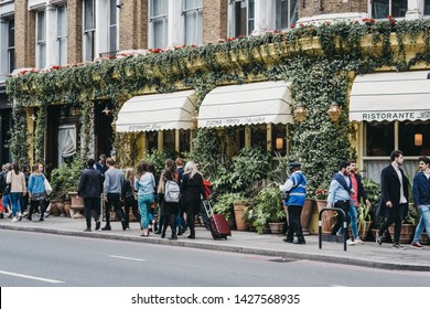 London, UK - June 15, 2019: People walking past Gloria, Italian restaurant in Shoreditch, London, famous for ivy-covered exterior walls and numerous plants in terracotta pots outside.