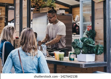 London, UK - June 15, 2019: Women ordering food from a stall inside Spitalfields Market, one of the finest surviving Victorian Market Halls in London with stalls offering fashion, antiques and food.