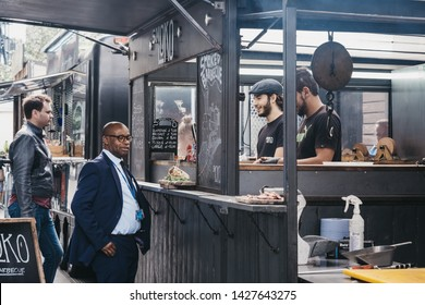 London, UK - June 15, 2019: Man buying food from Smokoloco stall inside Spitalfields Market, one of the finest Victorian Market Halls in London with stalls offering fashion, antiques and food.