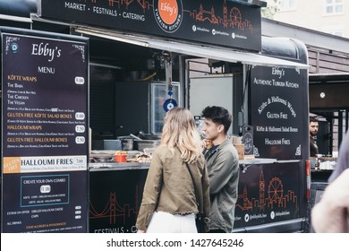 London, UK - June 15, 2019: People ordering food from Ebbys stall inside Spitalfields Market, one of the finest Victorian Market Halls in London with stalls offering fashion, antiques and food.