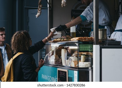 London, UK - June 15, 2019: Woman buying food from a stall inside Spitalfields Market, one of the finest surviving Victorian Market Halls in London with stalls offering fashion, antiques and food.
