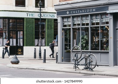 London, UK - June 15, 2019: People walking past Cult & Bloom hair salon in Shoreditch, a trendy area of Londons East End that is home to an array of interesting markets, bars and restaurants.