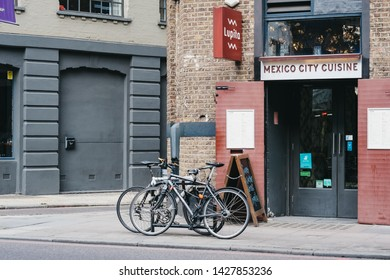 London, UK - June 15, 2019: Bikes parked on a street by Lupita Mexican restaurant in Shoreditch, a trendy area of Londons East End that is home to an array of markets, bars and restaurants.