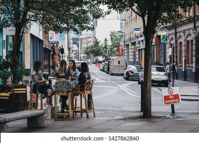 London, UK - June 15, 2019: Women sitting at the outdoor tables of a restaurant in Shoreditch, a trendy area of Londons East End that is home to an array of markets, bars and restaurants.