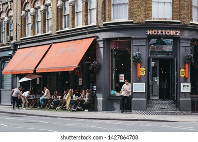 London, UK - June 15, 2019: People sitting at the outdoor tables of Hoxton 7 bar in Shoreditch, a trendy area of Londons East End that is home to an array of markets, bars and restaurants.