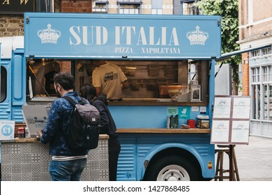 London, UK - June 15, 2019: People buying food from a Sud Italia pizza stall inside Spitalfields Market, one of the finest Victorian Markets in London with stalls offering fashion, antiques and food.