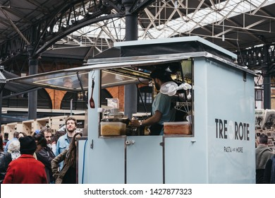London, UK - June 15, 2019: People buying food from Tre Rote pasta stall inside Spitalfields Market, one of the finest Victorian Markets in London with stalls offering fashion, antiques and food.