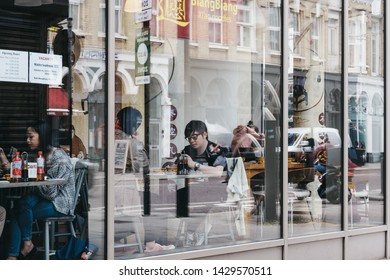 London, UK - June 15, 2019: View through the window of people inside Xian Biang Biang restaurant in Shoreditch, a trendy area of Londons East End that is home to an array of bars and restaurant.