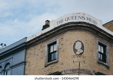 London, UK - June 15, 2019: Low angle view of Queens Head pub name against blue sky in Shoreditch, a trendy area of Londons East End that is home to an array of markets, bars and restaurants.