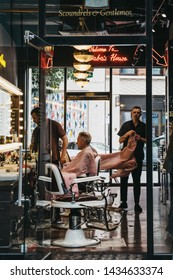 London, UK - June 15, 2019: Man getting haircuts inside Barber Barber, an award-winning barbershop inside Spitalfields Market, London.