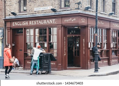 London, UK - June 15, 2019: Employee throwing away rubbish outside the English Restaurant in Shoreditch, a trendy area of Londons East End that is home to an array of markets, bars and restaurants.
