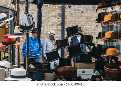 London, UK - June 15, 2019:People behind hats on sale at stall inside Spitalfields Market, one of the finest surviving Victorian Market Halls in London with stalls offering fashion, antiques and food.
