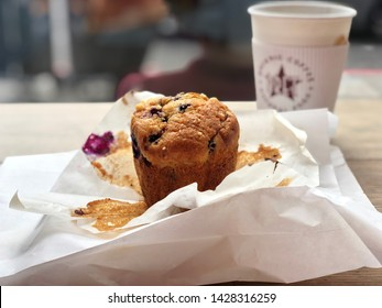 LONDON, UK - JUNE 19, 2019: A Berry muffin and paper packaging with coffee inside a Pret A Manger cafe in London, UK.