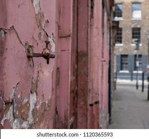 London UK, June 2018. Detail on the facade of a red painted traditional Huguenot weaver's house on Princelet Street, Spitalfields, East London. Frontage is weathered and dilapidated.