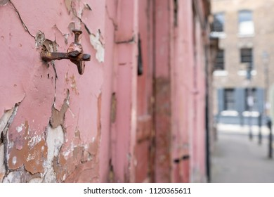 London UK, June 2018. Detail on the facade of red painted traditional Huguenot weaver's house at 4 Princelet Street, Spitalfields, East End. Frontage is weathered and dilapidated with peeling paint.