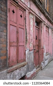 London UK, June 2018. Exterior facade of red / pink painted traditional Huguenot weaver's house at 4 Princelet Street, Spitalfields, East London. Frontage is weathered, dilapidated, and characterful.