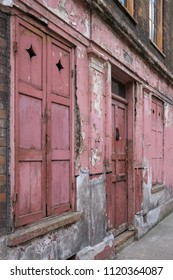 London UK, June 2018. Exterior facade of red painted traditional Huguenot weaver's house on Princelet Street, Spitalfields, East London. Frontage is weathered and dilapidated, and characterful.