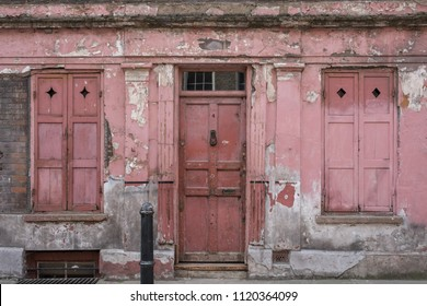 London UK, June 2018. Exterior facade of red / pink painted traditional Huguenot weaver's house at 4 Princelet Street, Spitalfields, East London. Paint and plaster work is weathered and peeling.