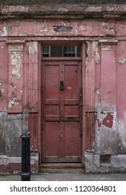 London UK, June 2018. Part of the exterior facade of red painted traditional Huguenot weaver's house on Princelet Street, Spitalfields, East London. Frontage is weathered and dilapidated.