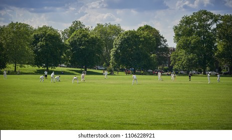 London, UK - June, 2018. People playing cricket in park in South London