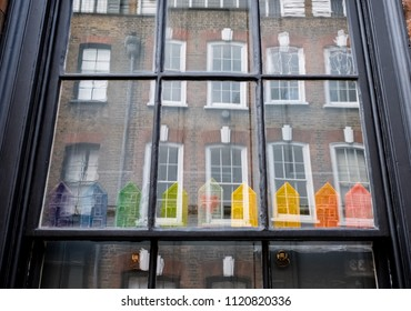 London UK, June 2018. Window of a traditional Huguenot weaver's house on Princelet Street, Spitalfields, East London, showing reflection of buildings opposite and quirky rainbow coloured model houses.