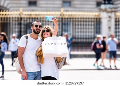 London, UK - June 21, 2018: Romantic young happy smiling couple standing taking selfie in front of gold, golden Buckingham Palace closeup fence, topshop shopping bag