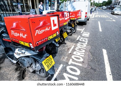 London, UK - June 21, 2018: Row of many Pizza Hut online delivery scooters, motorcycles parking, parked by road street curb in Pimlico with nobody