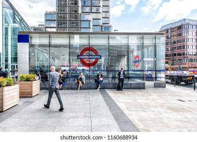 London, UK - June 21, 2018: Victoria Underground tube station outside outdoors with modern steel, glass windows, business people, businessman, women, men walking on sidewalk, sitting, talking on phone