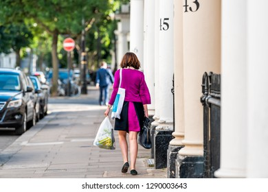 London, UK - June 21, 2018: Neighborhood district of Pimlico with terraced housing buildings and numbers on columns with woman walking carrying Waitrose grocery bags