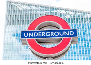 London, UK - June 21, 2018: Closeup of Underground tube metro blue and red sign in Victoria on street road in center of downtown city with modern glass skyscraper building isolated logo