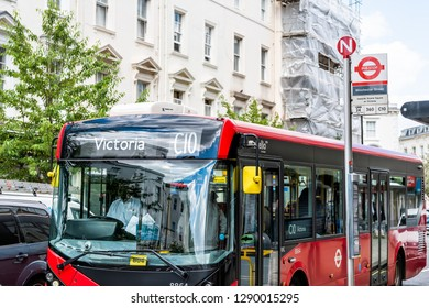 London, UK - June 21, 2018: Street road with front of red public transportation bus at stop on Winchester street and direction sign for Victoria in Pimlico