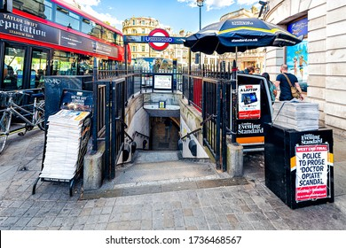 London, UK - June 21, 2018: Underground station in Charing cross exterior with sign for news newspaper stand and red double decker bus in summer