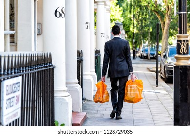 London, UK - June 22, 2018: Neighborhood district of Pimlico, Gloucester Street, businessman man carrying grocery shopping bags after work in evening walking home by architecture traditional style