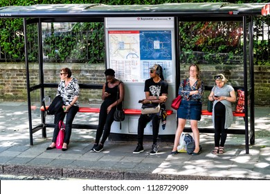 London, UK - June 22, 2018: People women waiting for bus at stop tired during day standing under cover, signs for Bayswater Queensway Underground tube metro on street road in city