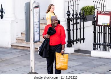 London, UK - June 22, 2018: Neighborhood district of South Kensington man carrying Sainsbury's grocery shopping bags waiting to cross street, bus stop