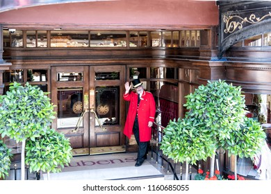London, UK - June 22, 2018: Porter, doorman in traditional attire, clothing, hat, red gown, coat standing at Rubens hotel, inn entrance waving hand
