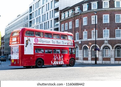 London, UK - June 22, 2018: Iconic, classic red double decker bus driving, turning on intersection with people sitting, eating during Afternoon Tea Tour