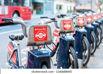 London, UK - June 22, 2018: Many Santander Cycles red bikes for hire, rent, rental standing, parked at docking station in downtown in row by street, road, sidewalk