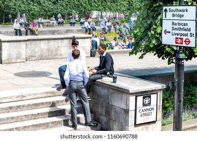 London, UK - June 22, 2018: Young three businessmen sitting in Festival Gardens by St Paul's Cathedral, Cannon Street, churchyard during lunch break, talking