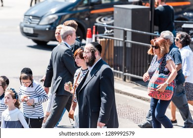 London, UK - June 22, 2018: High angle view of many people tourists, Jewish family walking at crosswalk to cross street closeup during day road in city crowded packed busy