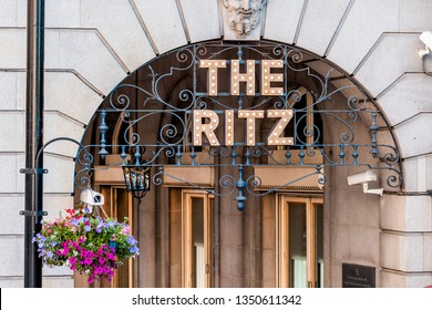 London, UK - June 22, 2018: Piccadilly Circus Regent street with closeup of sign entrance to the Ritz hotel with hanging basket flower decoration in summer and nobody
